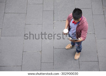 High angle view of a Chinese man standing on city street using a tablet device. - stock photo