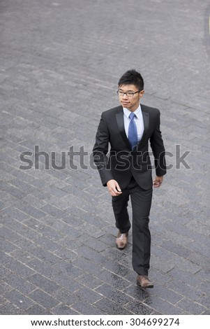 High angle view of a confident asian businessman walking in the city. - stock photo