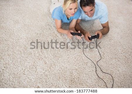 High angle view of a couple playing video games on area rug at home - stock photo