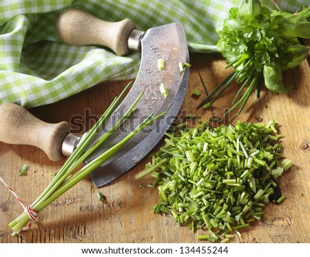 High angle view of a curved kitchen rocker blade used for chopping a pile fresh chives for use as an ingredient in cooking and salads