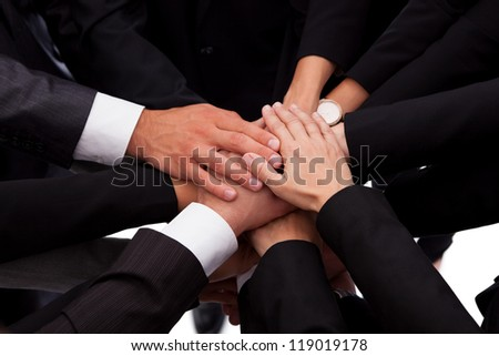 High angle view of a diverse group of people in a business team with their hands one on top of the other - stock photo