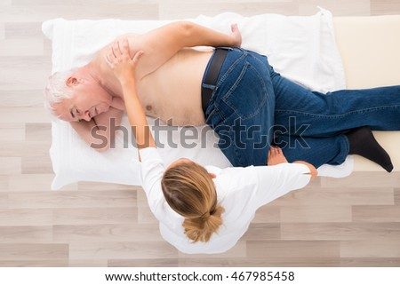 High Angle View Of A Female Masseur Doing Massage On Senior Man