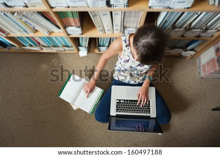 High angle view of a female student sitting against bookshelf with laptop on the library floor - stock photo
