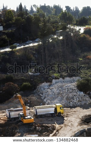 High angle view of a front-end loader doing earthworks on a hill, gnawing at the hillside and loading the rocks and dirt onto a heavy truck; preparing the ground for construction. - stock photo