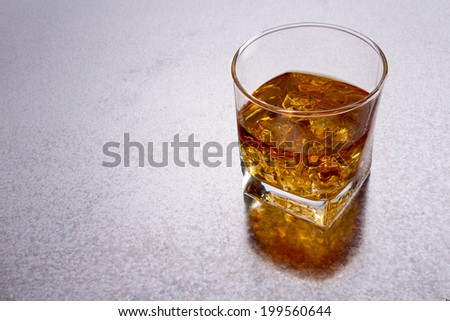 High angle view of a glass of whiskey on a shiny textured metal bar counter with copyspace to the left and a reflection