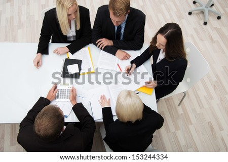 High angle view of a group of young successful businesspeople in a meeting analyzing and planning a new strategy - stock photo