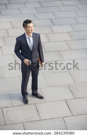 High angle view of a happy Asian businessman looking away. - stock photo