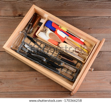 High angle view of a kitchen drawer on a rustic wooden table. The drawer is full of wooden spoons, knives, whisks spatulas, and other household kitchen items. - stock photo