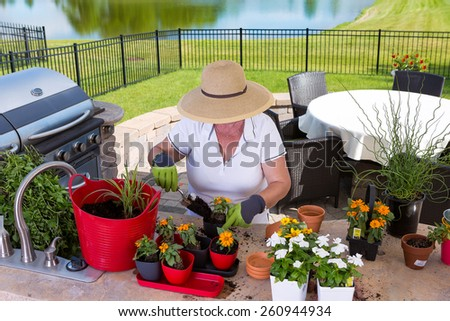 High angle view of a lady gardener wearing a wide-brimmed straw sunhat potting up new plants on an outdoor patio at the counter in her summer kitchen - stock photo