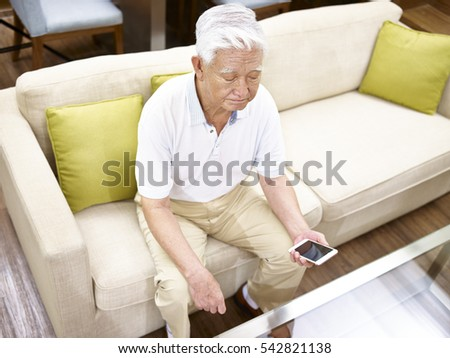 high angle view of a lonely asian senior sitting on couch with cellphone in hand.