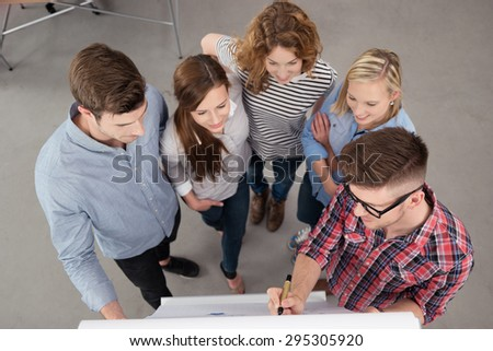 High Angle View of a Male Team Leader Presenting Something on a Poster to the Group Inside the Office. - stock photo