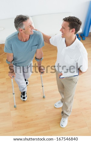 High angle view of a male therapist and disabled patient with reports in the gym at hospital