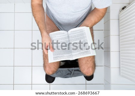 High Angle View Of A Man In Toilet Reading Book