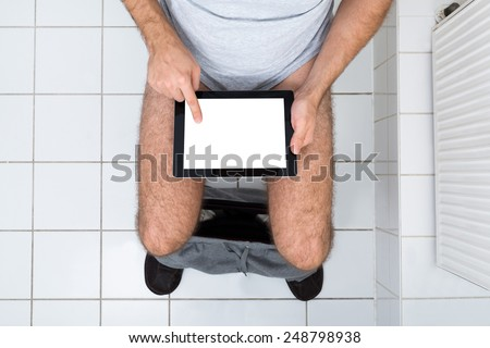 High Angle View Of A Man In Toilet Using Digital Tablet - stock photo