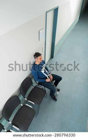 High Angle View Of A Man Sitting On Chair With Crutches In Hospital - stock photo