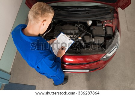 High Angle View Of A Mechanic Standing Near Car Writing On Clipboard In Garage - stock photo