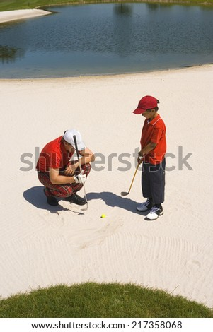 High angle view of a mid adult man giving golf training to his son - stock photo