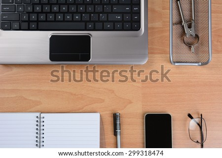 High angle view of a modern business desk with laptop, cell phone, pen, paper, glasses, and other office items. Horizontal format with copy space in the middle.  - stock photo
