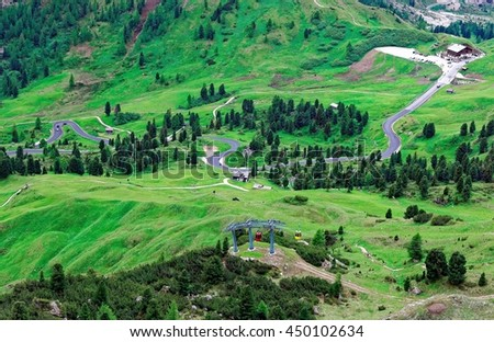 High angle view of a mountain highway meandering through a beautiful green valley and a cable way by the mountainside ~ Magnificent landscape of Dolomites Mountains in Passo Gardena, South Tyrol Italy - stock photo
