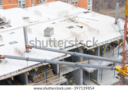 High angle view of a new high-rise building under construction in a city showing the open concrete framework of the floors stacked with timber or lumber - stock photo