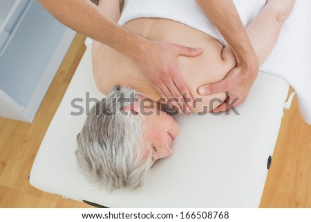 High angle view of a physiotherapist massaging a senior woman's back in the medical office - stock photo
