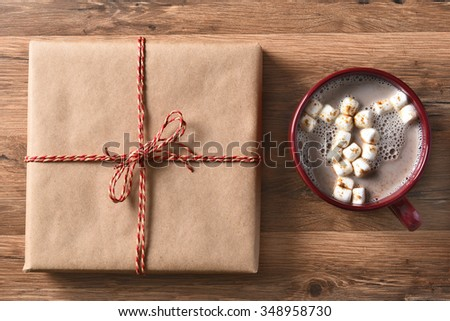 High angle view of a plain brown paper wrapped Christmas Present next to a large mug of hot cocoa with marshmallows.