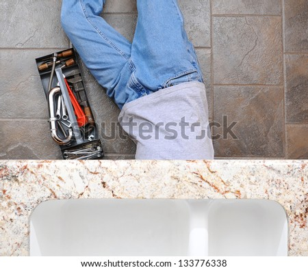 High angle view of a plumber laying under a kitchen sink. Man is unrecognizable with a tool box next to him. - stock photo
