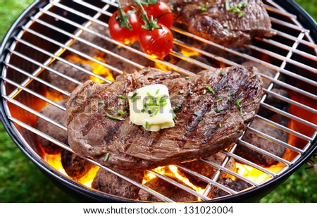 High angle view of a portion of lean steak topped with butter and herbs grilling over a glowing fire in a portable barbecue outdoors on grass - stock photo