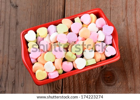 High angle view of a red rectangular candy bowl filled with Valentine's Day Candies. The heart shaped candy is blank and ready for your message. - stock photo