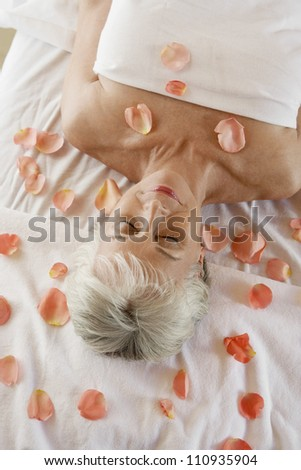 High angle view of a senior woman surrounded by petals relaxing on message table - stock photo