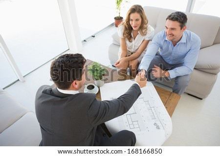 High angle view of a smiling young couple in meeting with a financial adviser at home - stock photo