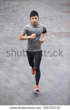 High angle view of a Sporty fit Asian man jogging on street listening to music on smart phone. Male fitness concept.  