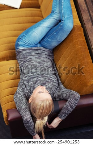 High angle view of a young blond woman relaxing on a sofa at home lying on her back with her feet raised looking thoughtfully into the air