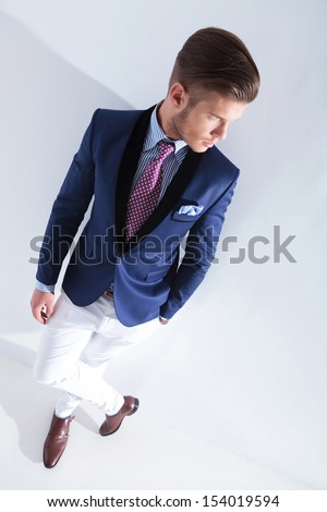high angle view of a young business man looking away from the camera while holding a hand in his pocket. on a gray background