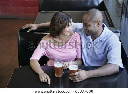High angle view of a young couple sitting at a restaurant table with glasses of beer