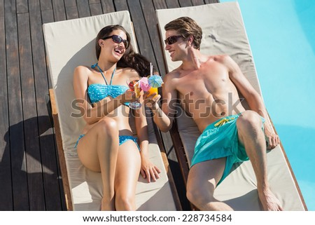 High angle view of a young couple with drinks on sun loungers by swimming pool - stock photo