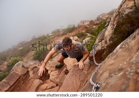 High angle view of a young male hiker climbing rocks on a nature trail on a mountain - stock photo