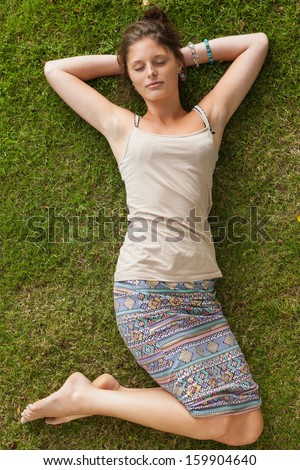 High angle view of a young woman resting on grass at the park - stock photo