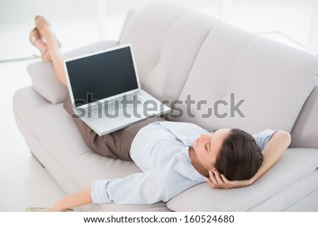 High angle view of a young woman with laptop lying on sofa at home - stock photo