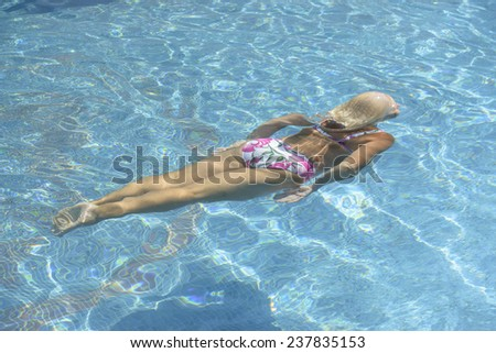 High angle view of aged woman that is swimming underwater in bright blue water of pool.