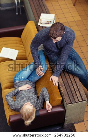 High angle view of an affectionate young couple relaxing in an apartment on a wooden bench and sofa as they spend a relaxing day with their books and magazines - stock photo