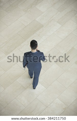 High angle view of an Asian businessman walking away. - stock photo