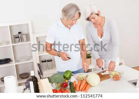 High angle view of an attractive middle-aged couple preparing a meal chopping vegetables in their kitchen - stock photo