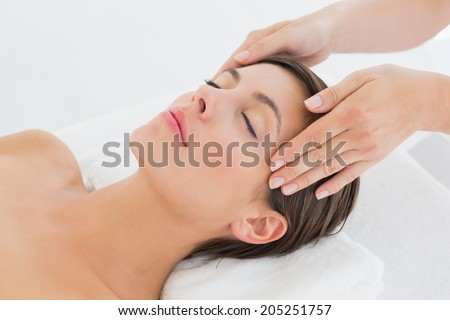High angle view of an attractive young woman receiving head massage at spa center