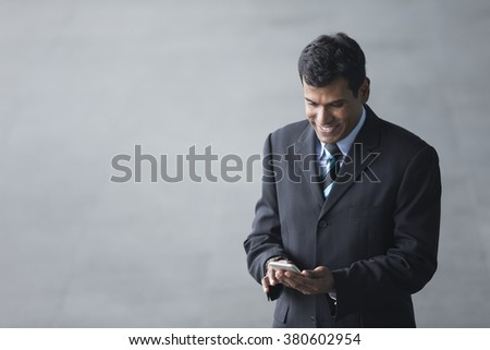 High angle view of an Indian businessman using his Smart phone outdoors in modern city. - stock photo