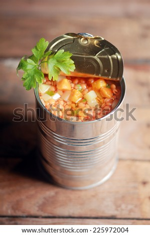 High angle view of an opened can of lentil and mixed vegetable soup garnished with fresh parsley for a delicious winter appetizer - stock photo