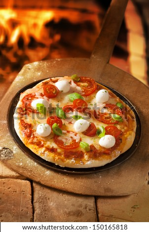 High angle view of an uncut crusty Italian pizza with cheese and tomato topped with mozzarella and fresh basil - stock photo