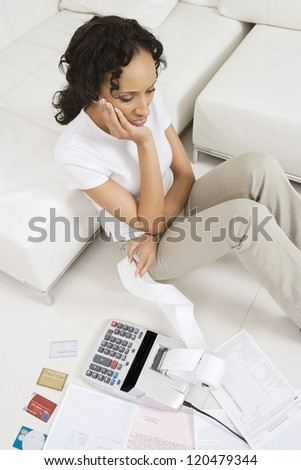 High angle view of an upset African American woman calculating her domestic expenses at home