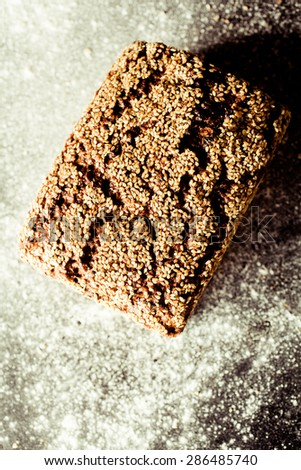 High Angle View of Artisinal Whole Grain Bread with Cracked Crust Surface and Covered with Sesame Seeds on Flour Covered Surface with Copy Space - stock photo