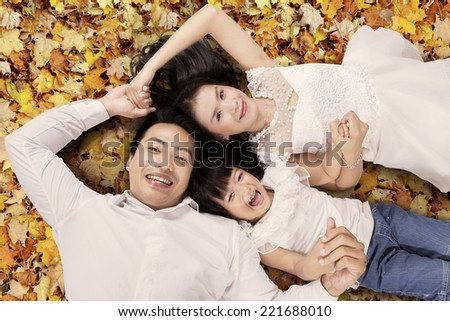 High angle view of asian family lying on autumn leaves, shot outdoors - stock photo